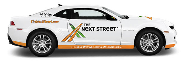 This is an image of a profile view a white car branded with The Next Street Driving School, the best driving school in Berlin.